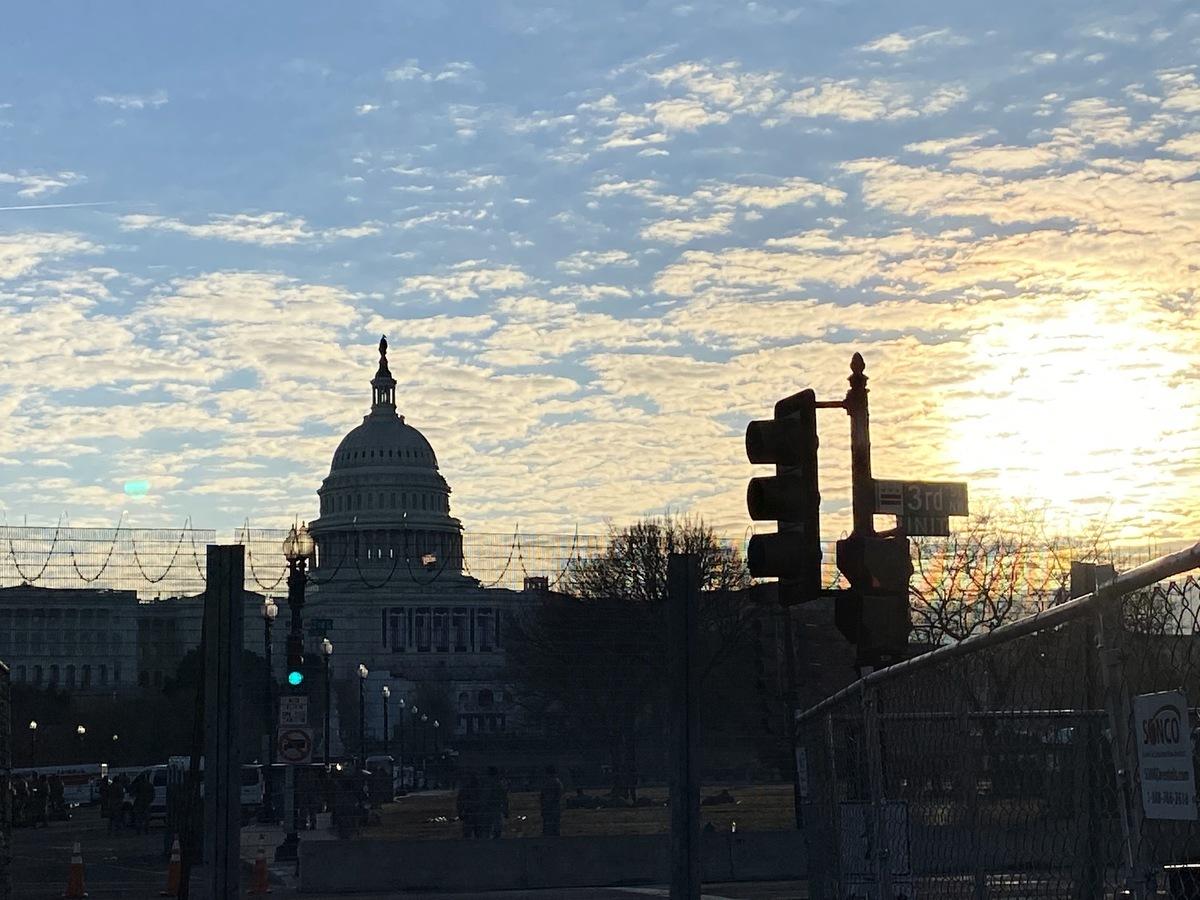 拜登上任第一天的舉動就引人質疑他言行不一致。圖為1月21日清晨國會大廈日出。(吳芮芮/大紀元)