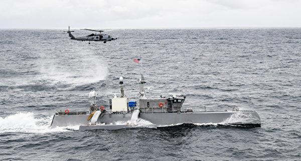 2021年4月21日,美軍的MH-60R海鷹直升機與無人水面艦艇在太平洋演練。(美國海軍)