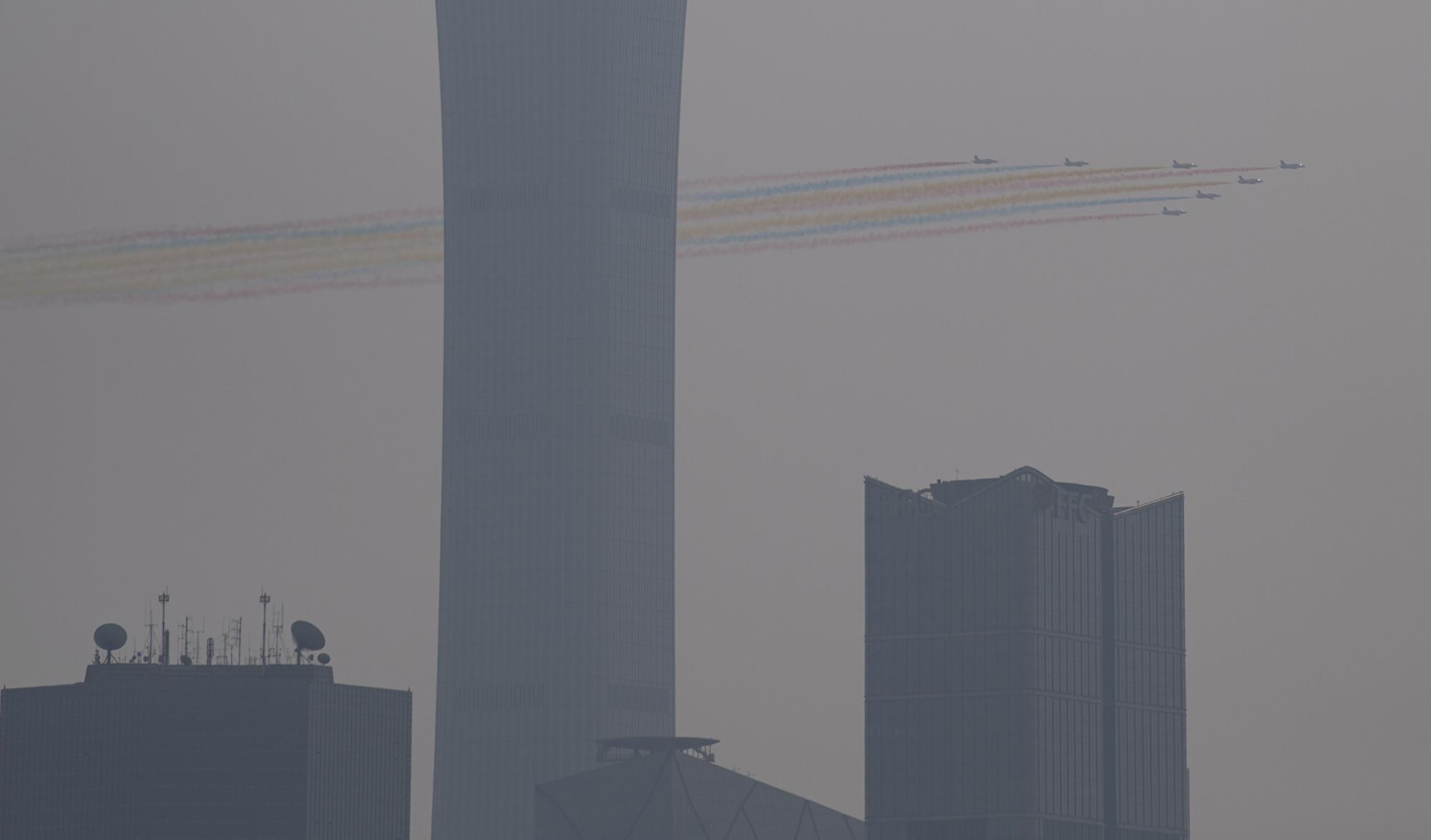 10月1日中共舉行閱兵式,北京城被陰霾籠罩。圖為天空中的彩色飛機陣。(NOEL CELIS / AFP)