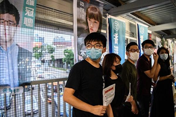 中共6月20日公佈港版國安法的細節,遭到黃之鋒等人的譴責。圖為香港民主活動人士黃之鋒等人5月22日在分發傳單,反對中共在香港強推的「港版國安法」。 (Anthony WALLACE / AFP)
