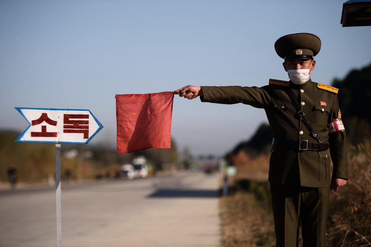 多個消息來源指出,北韓將中共肺炎病人關在集中營裏,任其活活餓死。圖為2020年10月29日,北韓元山市一個路口的公共安全官員在攔檢經過的車輛。(KIM WON JIN/AFP via Getty Images)