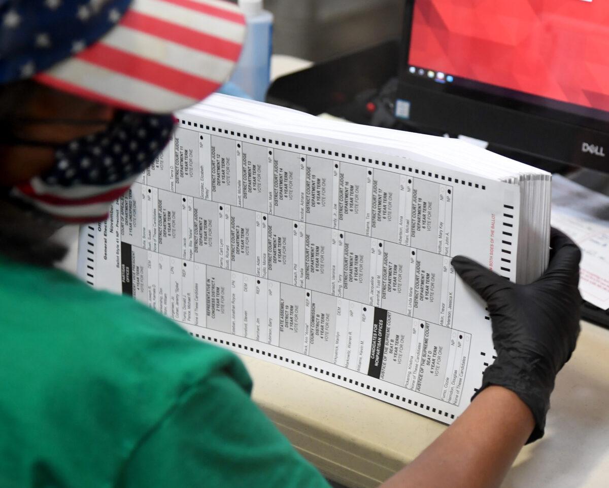 2020年11月7日,在內華達州北拉斯維加斯的克拉克縣選舉部門,一名選舉工作人員掃瞄郵寄的選票。(Ethan Miller/Getty Images)