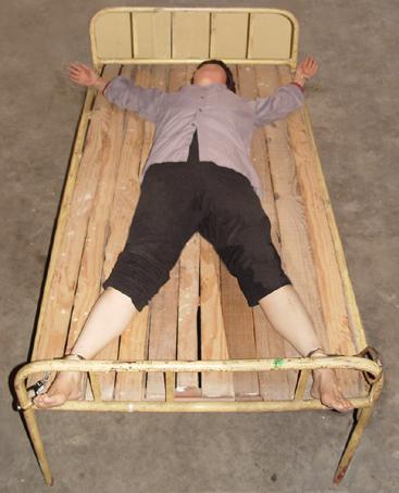 中共酷刑折磨示意圖:「死人床」。(明慧網)
