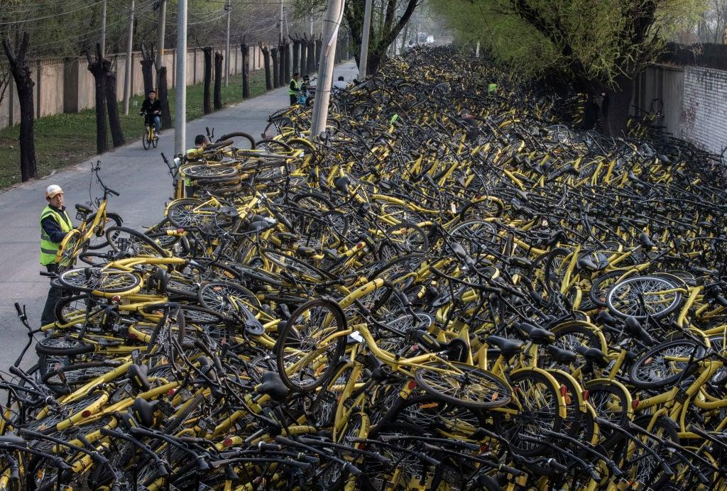 北京街頭的一名工人把一輛損壞的ofo小黃車放在一個臨時修理場所,那裡有成千上萬被廢棄的ofo共享單車。( Kevin Frayer/Getty Images)