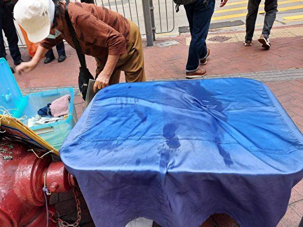 4月8日,香港銅鑼灣法輪功真相點的報紙遭惡徒潑濕。(法輪功學員周小姐提供)