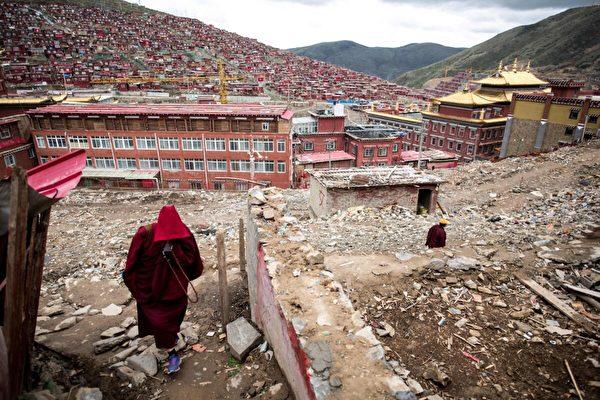 2017年5月29日,在中國西南部四川省色達縣的喇榮五明佛學院,一名尼姑走過被拆毀的房屋廢墟。(Johannes Eisele/AFP via Getty Images)