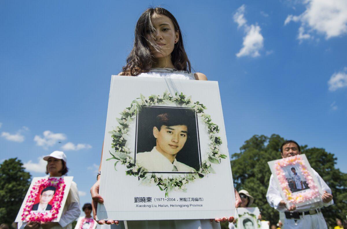 2014年7月17日,法輪功學員在華盛頓國會山遊行時手持遇害者照片。(Jim Watson/AFP via Getty Images)
