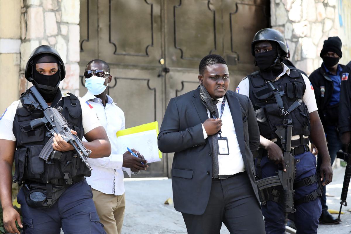 海地總統2021年7月7日若弗內爾‧莫伊茲(Jovenel Moise)凌晨在家中遇刺身亡,第一夫人也受傷。圖為海地首都太子港的總統府外,中央警察司法局(Direction Centrale de la Police Judiciaire,DCPJ)的警察帶著法醫巡邏。(VALERIE BAERISWYL/AFP via Getty Images)