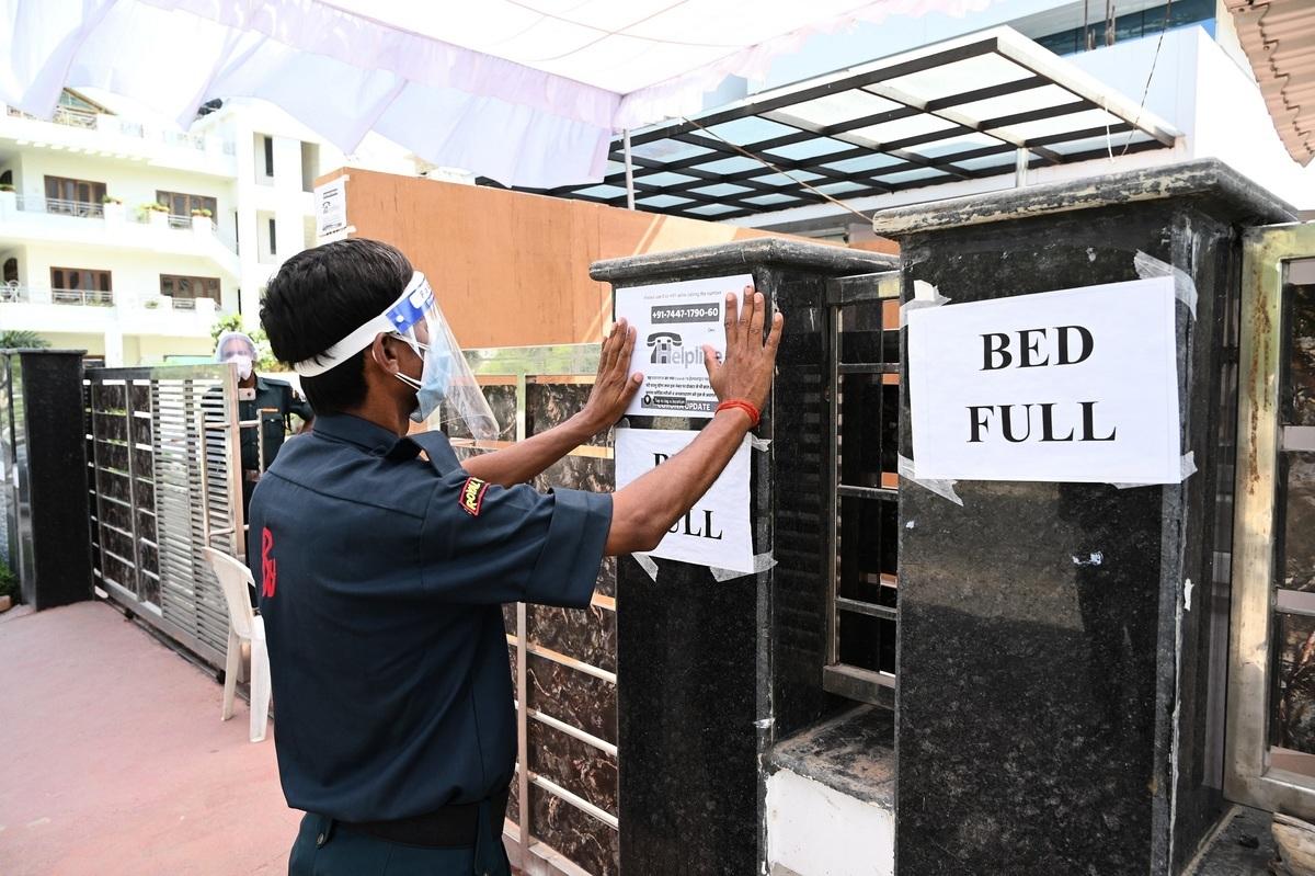 印度85歲老人達巴卡爾(Narayan Dabhalkar)在染疫後,自願讓出病床給年輕病人。圖為2021年4月22日,印度普拉亞格拉傑(Prayagraj)一所醫院的警衛貼出床位已滿的公告。(Shutterstock)