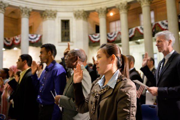 2014年5月22日,美國國土安全部長Jeh Johnson帶領移民在聯邦大廳(Federal Hall National Memorial)宣誓入籍。這75名移民來自世界31個國家,這一天,他們都成為了美國人,為此感到驕傲和自豪。(戴兵/大紀元)