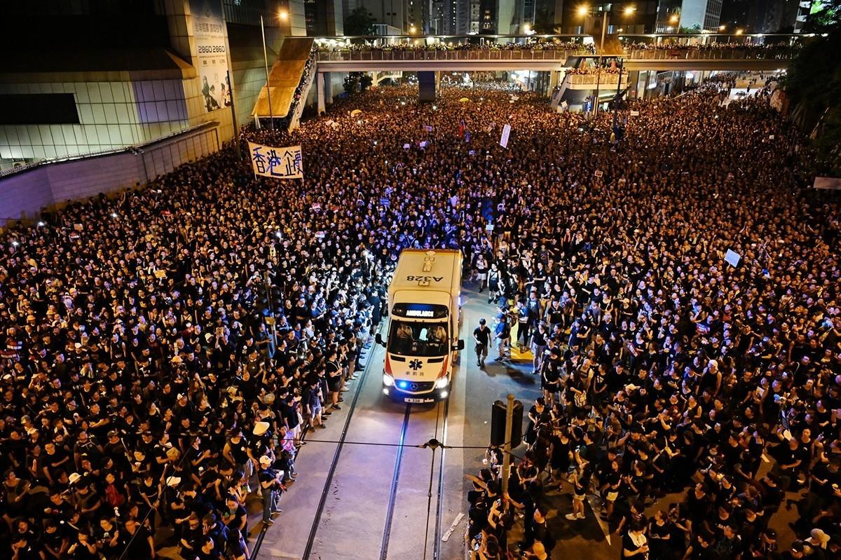2019年6月16日,香港200萬市民上街遊行抗議,反對政府強推《逃犯條例》。圖為遊行隊伍主動為救護車讓出通道,香港民眾的文明素養令全球讚歎。(HECTOR RETAMAL/AFP/Getty Images)