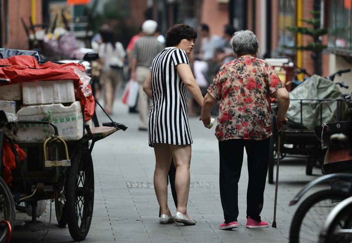 中國人口正在加速老齡化,中共過去的計劃生育惡果正在凸顯。圖為2013年7月1日,一對母女在上海一街道行走。(PETER PARKS/AFP/Getty Images)