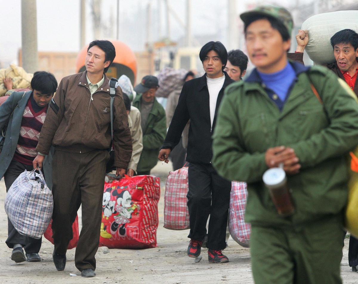 新書《低端中國:黨、土地、農民工,與中國即將到來的經濟危機》指,農民工成為中共拋棄的棋子 。圖為2005年10月26日中國的幾名農民工在趕路。(FREDERIC J.BROWN/AFP via Getty Images)