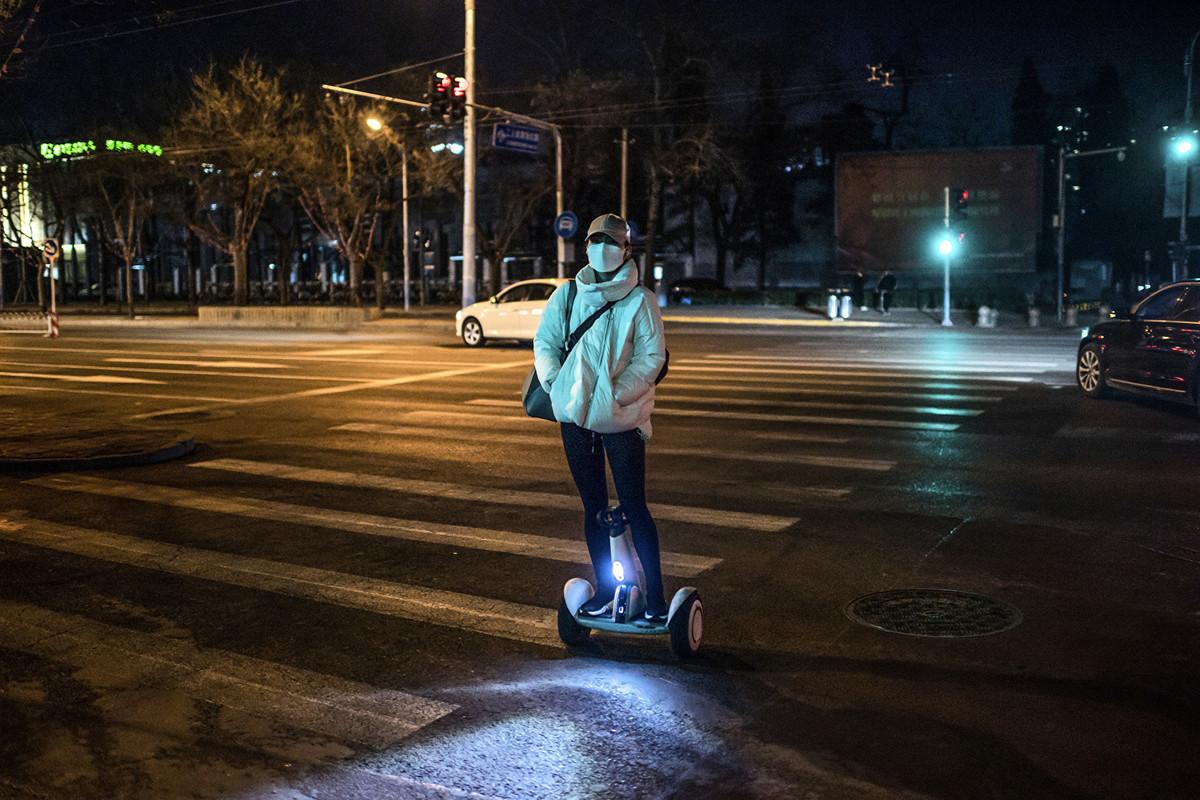 圖為2月21日北京街道上的一名婦女。(NICOLAS ASFOURI / AFP)
