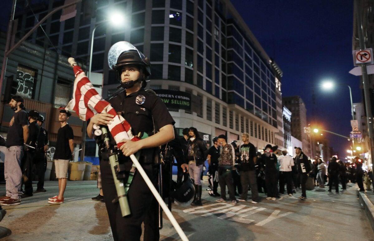 2020年6月2日,加利福尼亞州洛杉磯抗議者無視宵禁令繼續示威,遭到逮捕。圖中這名警察在保護一面美國國旗。 (Mario Tama/Getty Images)