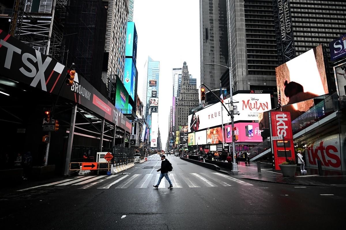 2020年3月13日,一名遊客穿越紐約時代廣場的第七大道。(Photo by JOHANNES EISELE/AFP via Getty Images)
