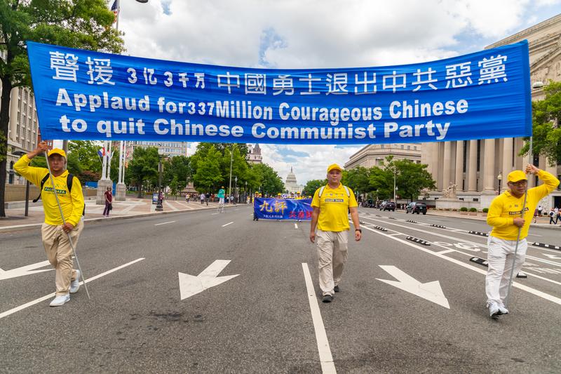 2019年7月18日,近二千名法輪功學員聚集在華盛頓DC舉行法輪功反迫害20周年大遊行。圖為法輪功學員以「聲援3億3千萬中國勇士退出中共惡黨」橫幅告訴世人中國正發生退黨大潮。(Mark Zou/大紀元)