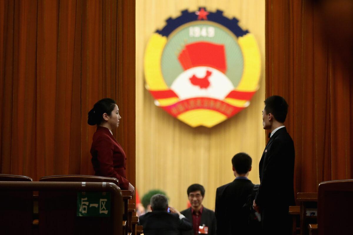 2013年3月11日,在中共政治協商會議全體會議在北京人民大會堂召開之前,一名女主持人站在會議室帷幕旁。政協是對中共統戰部工作至關重要的一個政府部門。(Feng Li/Getty Images)