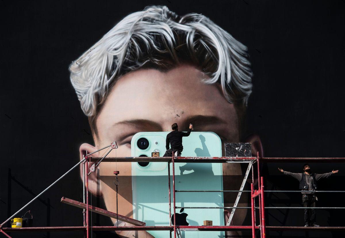 2020年10月1日,一位平面藝術家在柏林為智能手機製造商蘋果公司繪製壁畫廣告。(JOHN MACDOUGALL/AFP via Getty Images)