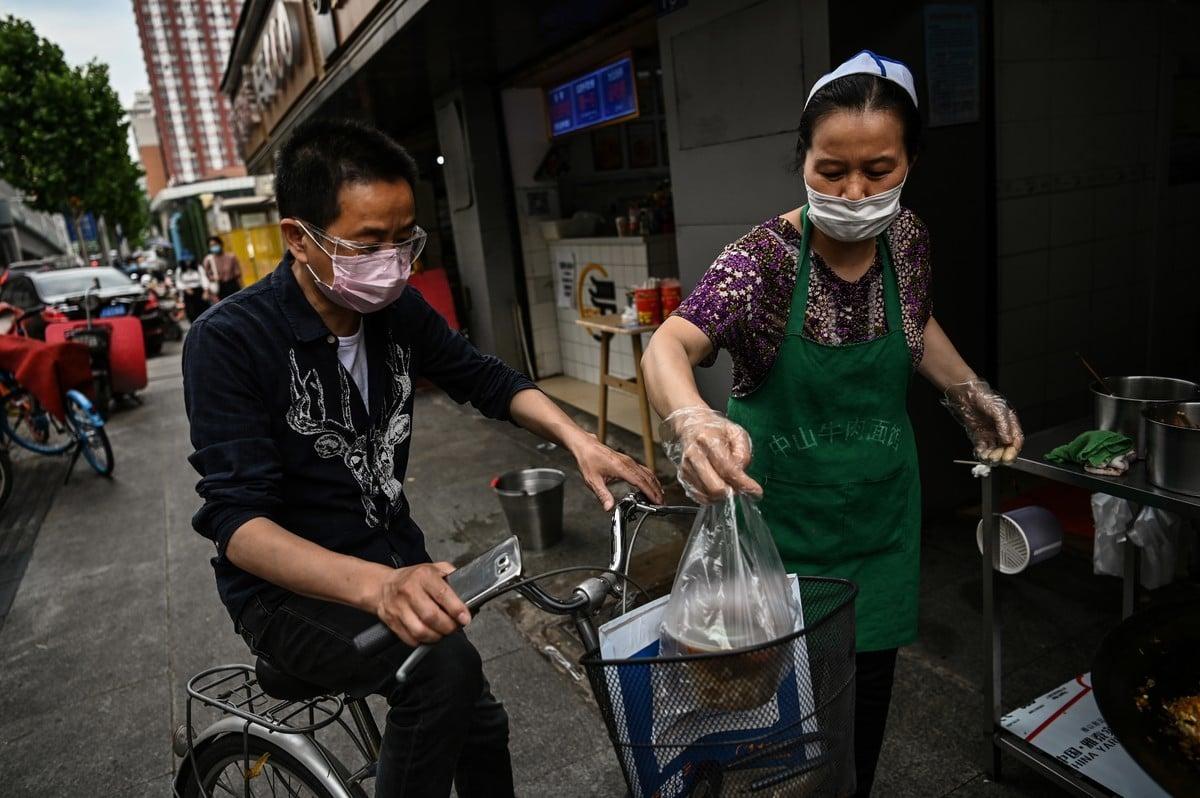 2020年5月13日,中國爆發中共病毒(俗稱武漢病毒、新冠病毒)疫情後,一名男子戴著口罩在武漢一家小賣部購買食物。(Photo by HECTOR RETAMAL/AFP via Getty Images)