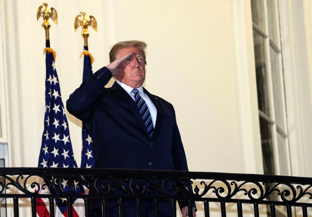 2020年10月5日傍晚,特朗普回到白宮,在白宮陽台上敬禮。(Photo by NICHOLAS KAMM / AFP)