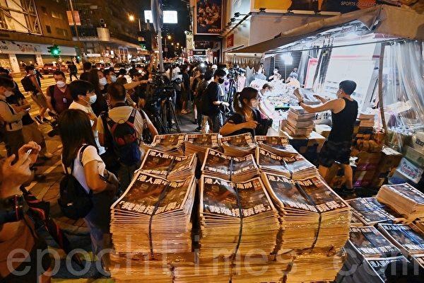香港《蘋果日報》2021年6月24日出版最後一份實體報紙,在旺角一個報攤,凌晨有巿民排隊準備購買。(宋碧龍/大紀元)