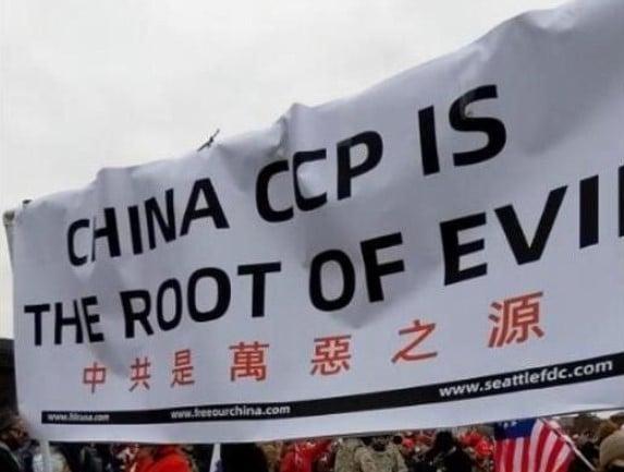 1月6日,金秀紅與友人舉著「中共是萬惡之源」的旗幟參與國會山莊前的集會。(金秀紅提供)
