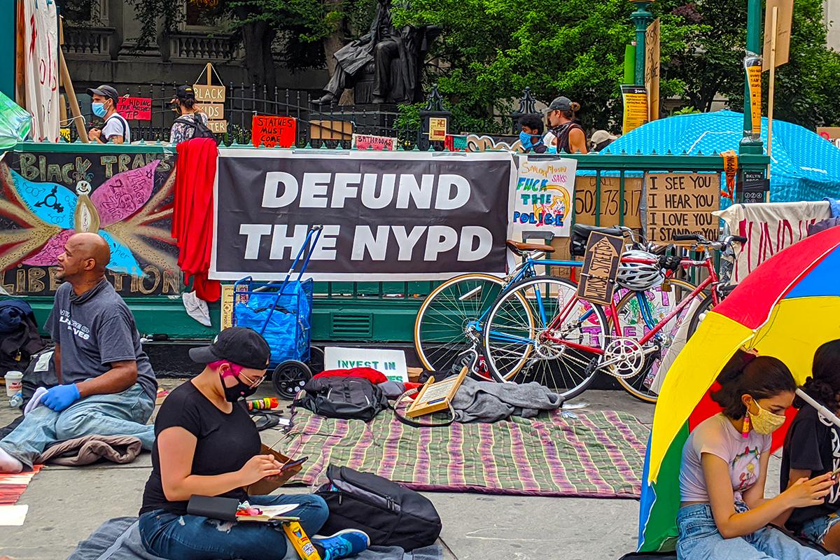 2020年6月26日,左傾團體「黑命貴」(BLM)佔領了紐約市政廳前廣場,而照片中間的標語寫著「撤資市警局」(defund the NYPD)。(黃小堂/大紀元)