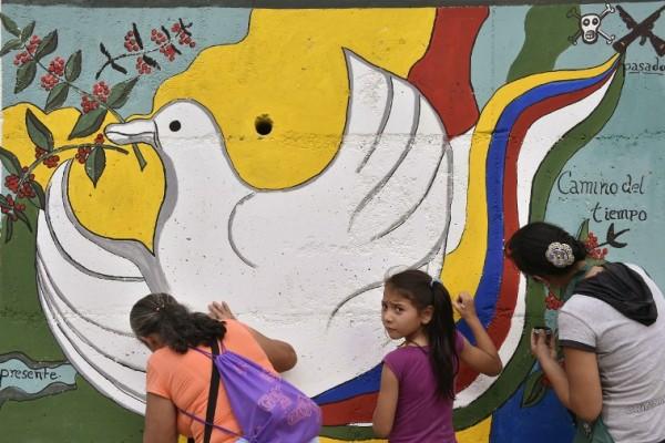 哥倫比亞政府與叛亂組織哥倫比亞革命軍(FARC)今天公佈修正版和平協議。哥國先前的公投,封殺了旨在終結長達52年內戰的和平協議。圖為哥倫比亞民眾在一處牆上畫上象徵和平的圖畫。(AFP PHOTO / GUILLERMO LEGARIA)