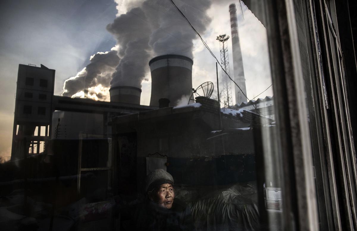 儘管中國一直對外宣傳,將致力於減少碳排放,但事實上中國仍對煤炭的高度依賴,也讓中國成為碳排放大國。最新民調也顯示,中國民眾將「污染」列為他們最關心的事務。圖為山西居民王努(音譯),看著窗外的燃煤電廠。照片攝於2015年11月26日。(Getty Images)