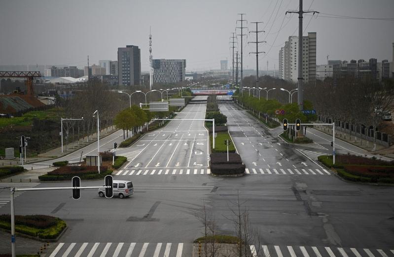 中共很多地方政府發出「倡議書」,讓公務員前往商場、餐館等場所消費,以此應對消費下滑的境況,並支持復工,引發民眾批評。圖為2020年3月4日,湖北武漢,街道上空蕩蕩。(NOEL CELIS/AFP via Getty Images)
