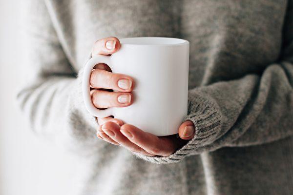 Etsy網購平台出售印有「我不需要治療,只需要去台灣」字樣的馬克杯。圖為一名女子手中拿著馬克杯,與本文無關。(Shutterstock)