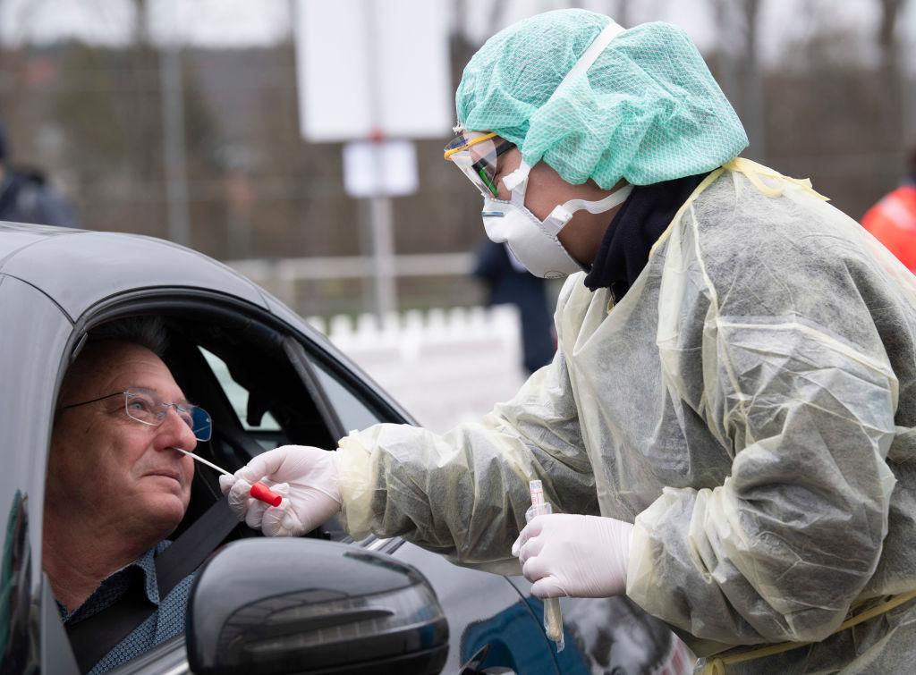 德國南部一名醫療助手正在檢查過往車輛,司機及乘客都要接受檢查。(THOMAS KIENZLE/AFP via Getty Images)