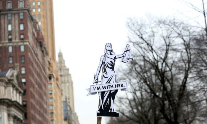 人們參加2020年1月18日在紐約市舉行的年度婦女遊行時,標語上寫著「我和她在一起」。(Yana Paskova/Getty Images)