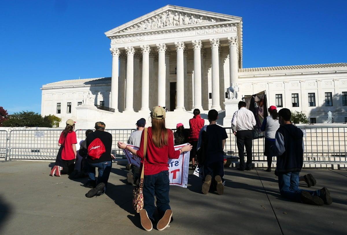 2020年11月7日,美國人在最高法院前為特朗普祈禱。前排最右邊低頭禱告的一男一女手持的是耶穌畫像。(李辰/大紀元)