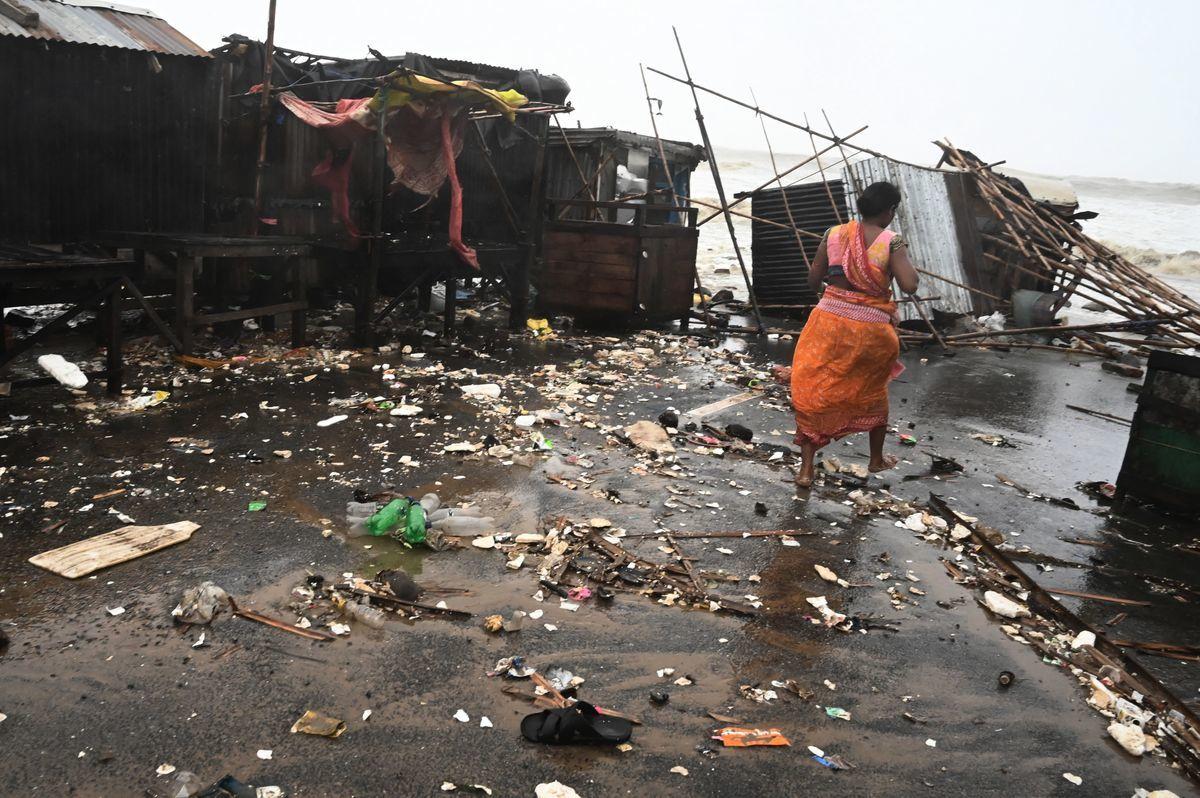 2021年5月26日,一位奧里薩邦巴拉索爾縣(Balasore)的居民在海濱地區的廢墟中行走。當時颶風雅斯(Yaas)正在向孟加拉灣的印度東海岸襲來。(DIBYANGSHU SARKAR/AFP via Getty Images)