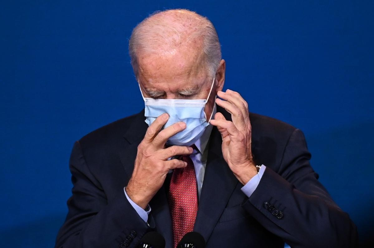 2020年10月28日,民主黨總統候選人喬·拜登(Joe Biden)在特拉華州威爾明頓(Wilmington)王后區(Queen)發表醫療保健演講時整理自己的口罩。(JIM WATSON/AFP via Getty Images)