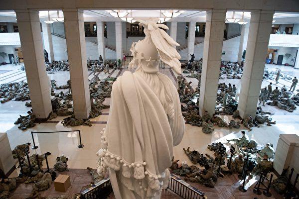 2021年1月13日,國民警衛隊成員躺在華盛頓國會山的國會遊客中心休息,眾議院當天辯論並投票,彈劾美國總統唐納德·特朗普。(SAUL LOEB/AFP via Getty Images)