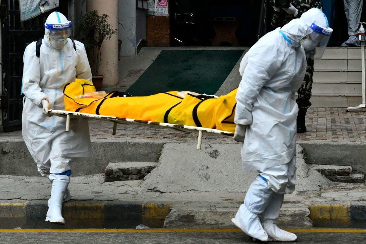 2021年5月5日,身穿個人防護用品(PPE)的尼泊爾陸軍人員將一名COVID-19(中共病毒引發的疾病)患者屍體送往加德滿都火葬場。(PRAKASH MATHEMA/AFP via Getty Images)