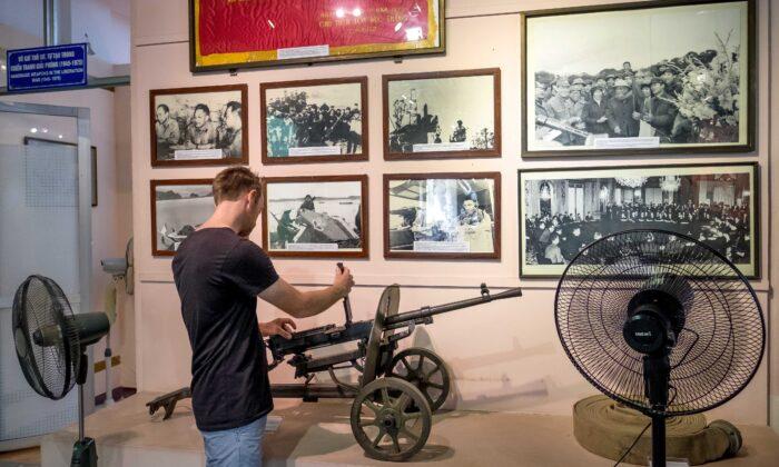 2016年5月25日,一名遊客在越南河內軍事歷史博物館把玩機關鎗。(Linh Pham/Getty Images)