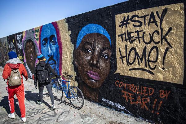 2020年3月23日,德國柏林婦女通過有關中共肺炎的街頭塗鴉與注意「留在家裡!」。(Maja Hitij/Getty Images)