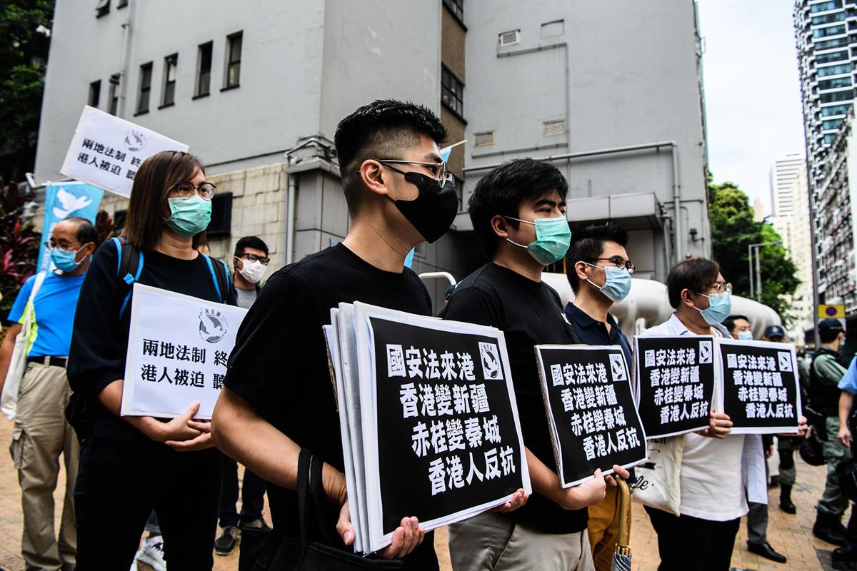 圖為2020年5月22日,香港民眾舉著標語牌,反對中共對香港強加國安法。(Anthony WALLACE / AFP)