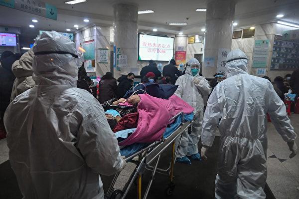 圖為2020年1月25日,武漢疫情嚴重時,醫療人員帶著病人到武漢紅十字會醫院。(Hector RETAMAL / AFP)