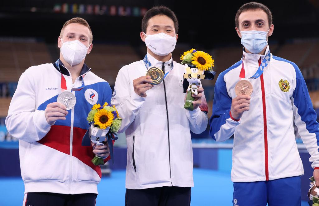 南韓選手申在煥(Shin Jea-hwan,中),2021年8月2日在東京奧運會男子跳馬決賽中獲得金牌。俄羅斯奧運隊選手丹尼斯‧阿布里亞金(Denis Ablyazin,左)獲得銀牌,亞美尼亞選手阿圖爾‧達夫泰安(Artur Davtyan)獲得銅牌。(Jamie Squire/Getty Images)