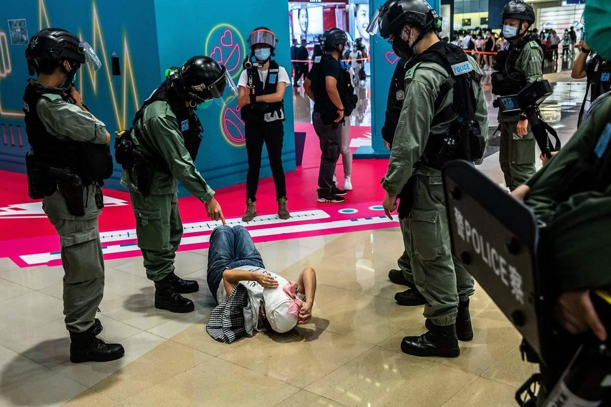 2020年7月6日,香港,購物中心地上躺著一位抗議的市民,幾位防暴警察圍著她。(ISAAC LAWRENCE/AFP via Getty Images)