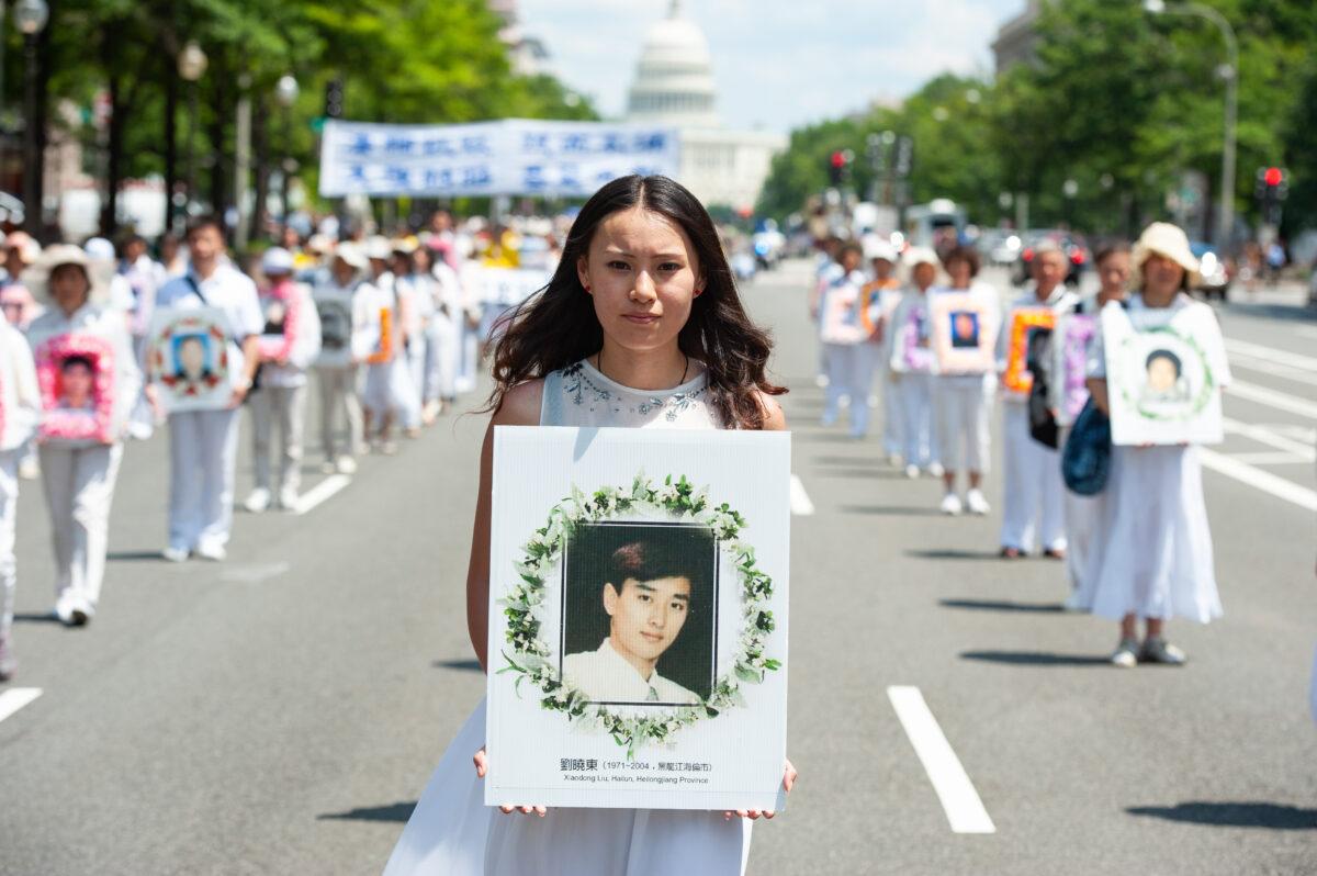 在2014年7月17日華盛頓舉行的一次遊行中,一位女士手捧一張男士的照片,該男士是被中共政權迫害致死的法輪功修煉者。(Larry Dye/大紀元)