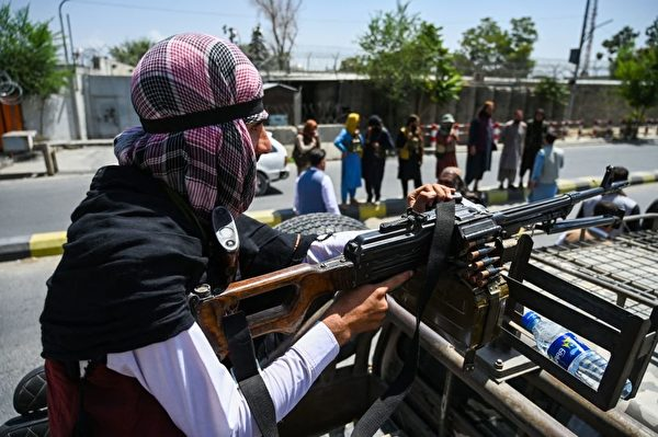 圖為一名塔利班武裝份子在車輛頂部配備機槍,他們在喀布爾的一條街道上巡邏。(WAKIL KOHSAR/AFP via Getty Images)