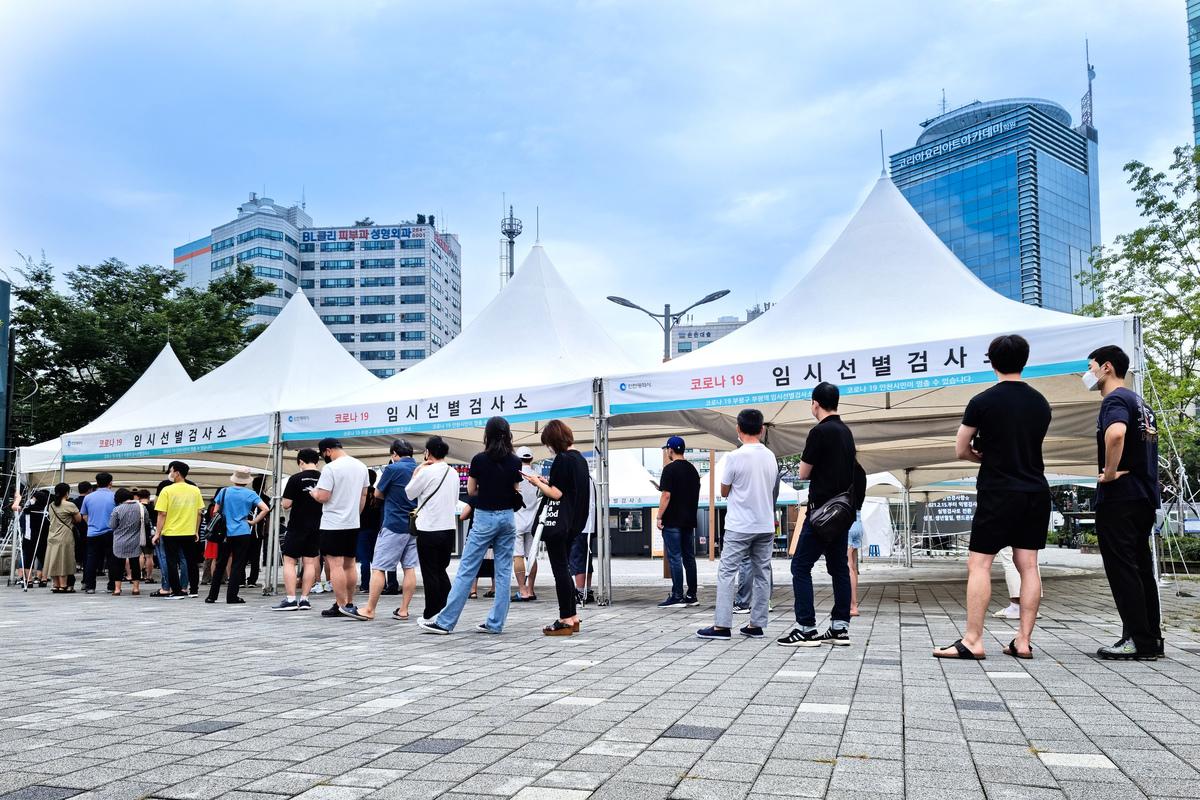 南韓市民排著長隊在仁川市富平地鐵站廣場等待進行檢測。(全景林/大紀元)