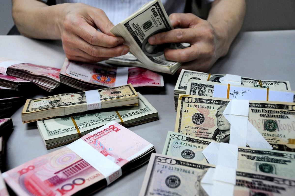 美國海曼資本管理公司創辦人巴斯在8月5日發推文說,人民幣的崩盤剛剛開始。圖為2011年8月10日,中國銀行在江蘇省的一家分行的員工在數鈔票。(VCG/VCG via Getty Images)