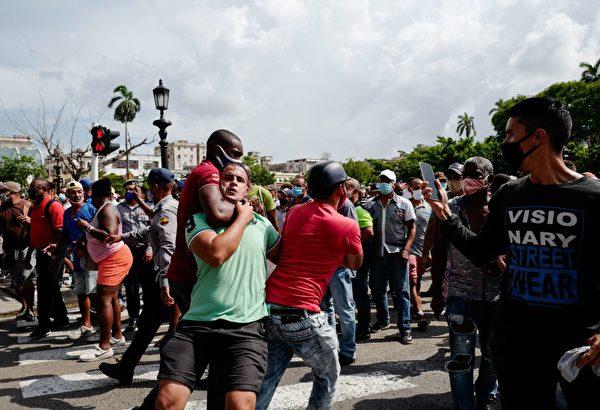 一名抗議男子被古巴當局的安全人員拉走。(Photo by ADALBERTO ROQUE/AFP via Getty Images)